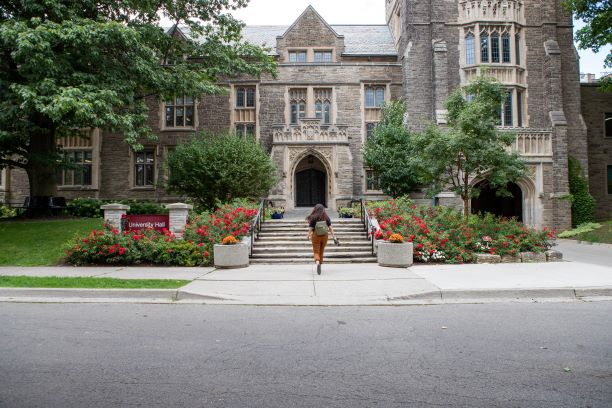 A shot of a student walking up the University Hall steps on campus