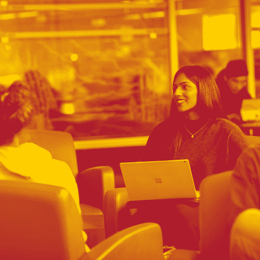 A yellow red duotone image of a student sitting in the library with a laptop