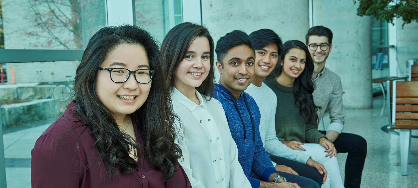 Six students sitting on a bench in the Health Sciences building