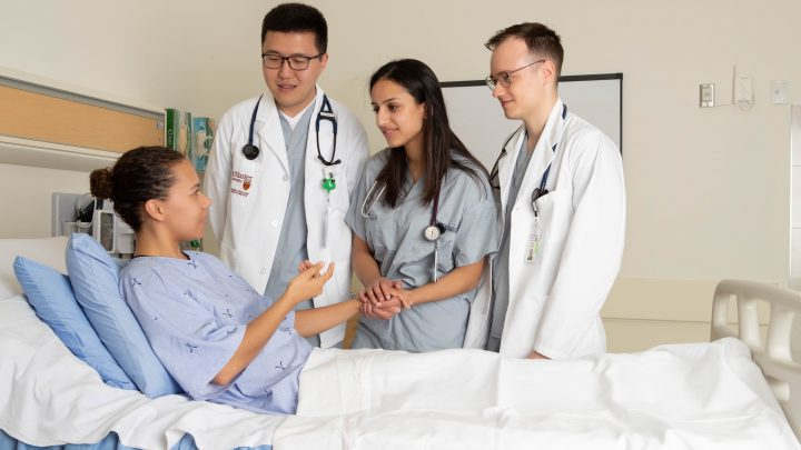 Three doctors talking to a patient in a hospital room