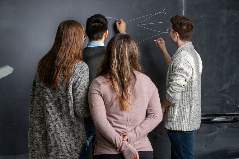 Four students drawing on a chalkboard