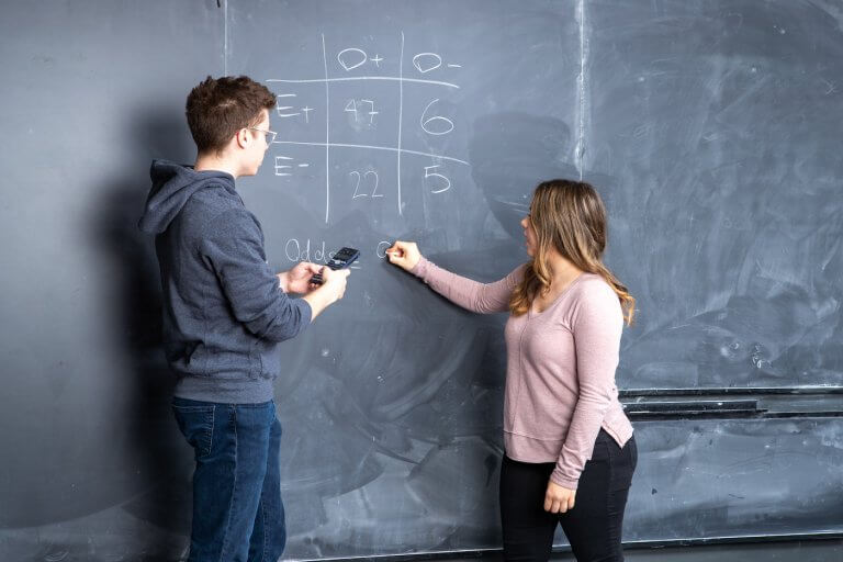Two students solving an equation on a chalkboard