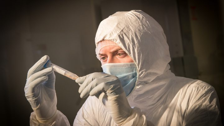 A man wearing personal protective equipment examining a vial