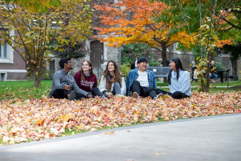 Five students sitting amongst a pile of fall leaves on campus