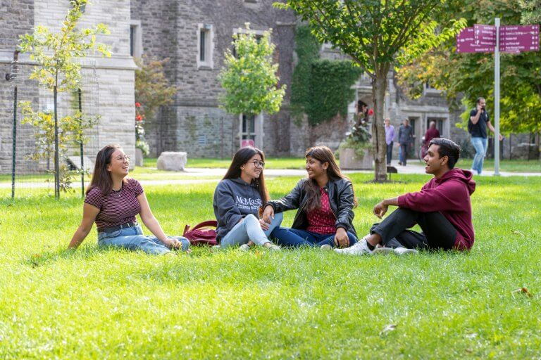 Four students sitting on BSB field and talking