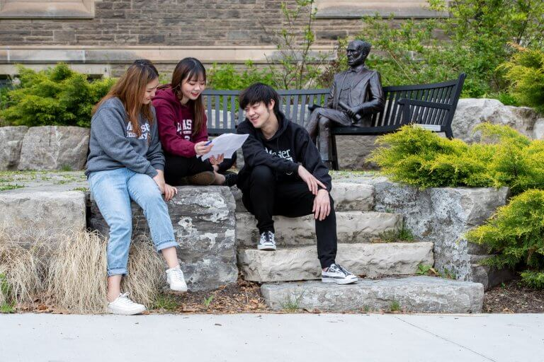 Three students sitting next to the William McMaster statue on campus, looking at a sheet of paper
