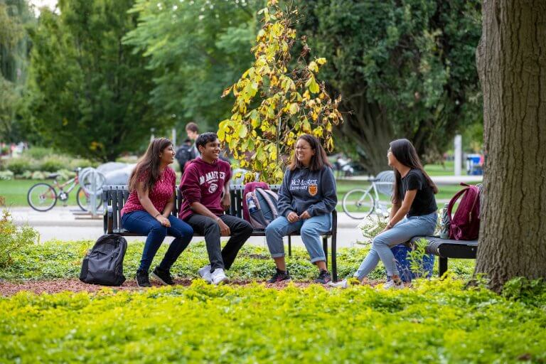 Four students sitting together on a bench on campus