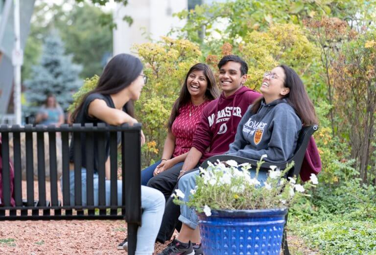 Four students laughing on a bench on campus