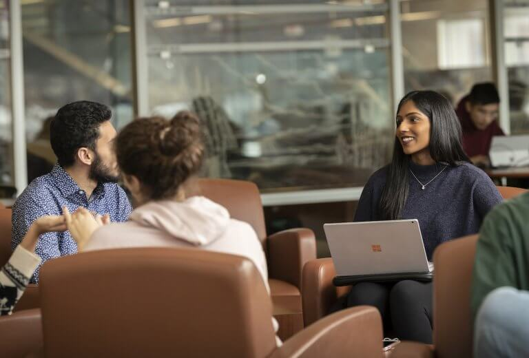 Three students sitting with their laptops and talking in the library
