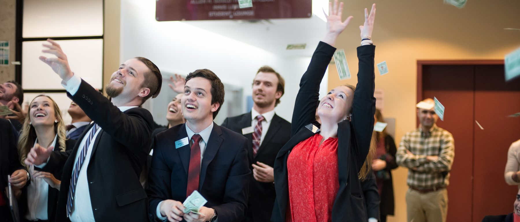 A group of business students throwing a pile of papers in the air