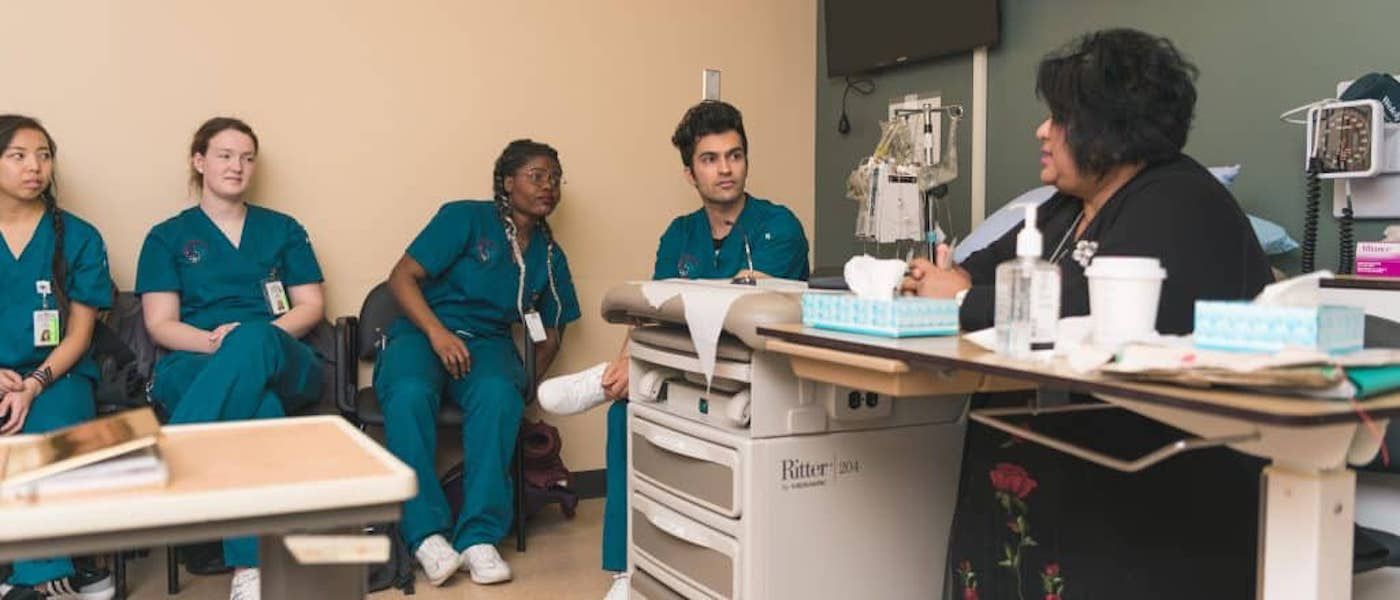 A group of medical radiation students paying attention to a woman talking