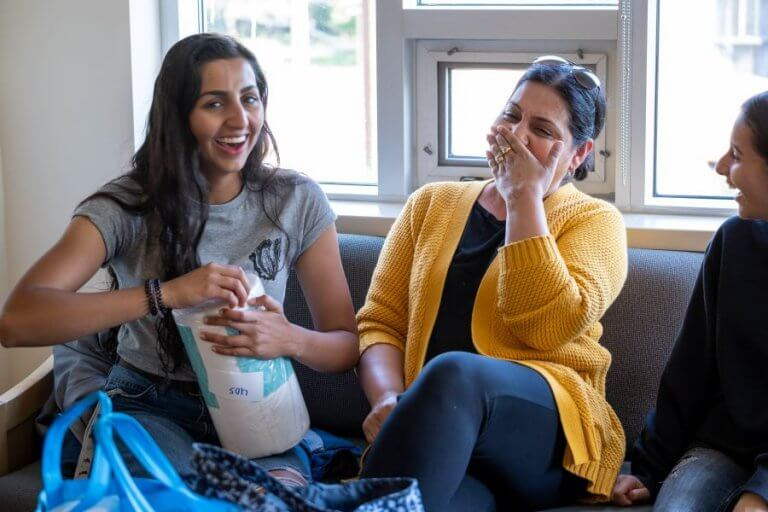 A student and parent sitting on a couch and laughing