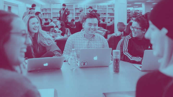 A blue yellow duotone image of a group of students at a table in a library