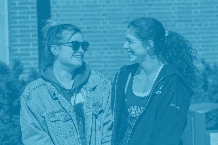 A blue green duotone image of two McMaster university students standing together for a picture on campus