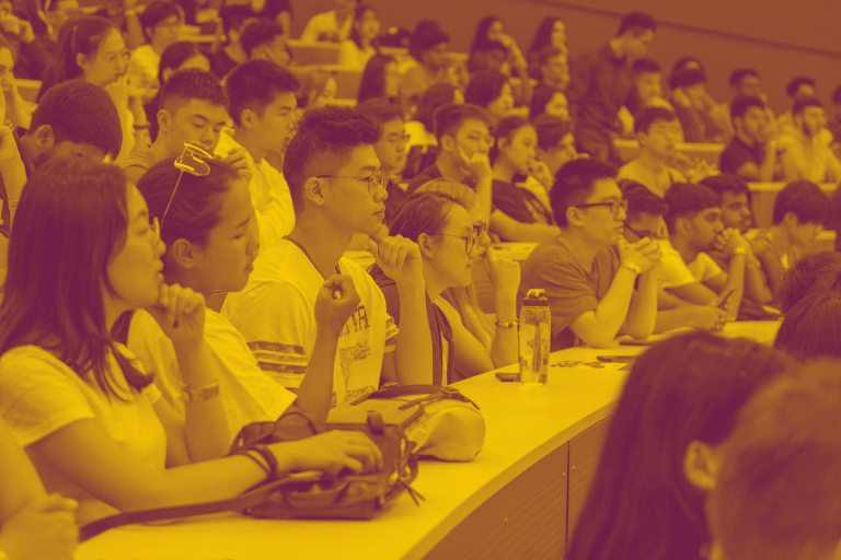 A maroon-yellow duotone image of a large group of students in a lecture hall