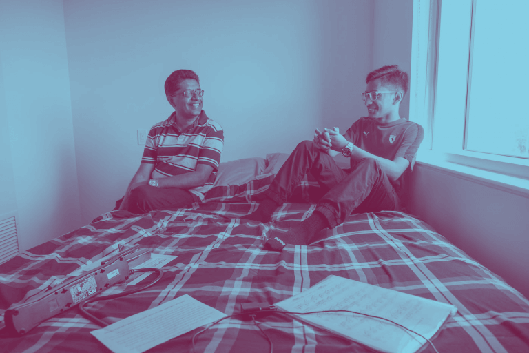 A blue-maroon duotone image of two McMaster students sitting on a student residence bed