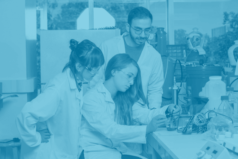 A blue duotone image of three McMaster students looking at a beaker in a science lab
