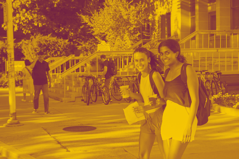 A yellow-maroon duotone image of two McMaster students walking outside student centre with coffee