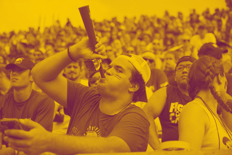 A yellow-maroon duotone image featuring a McMaster student in the crowded bleachers, blowing into a bullhorn
