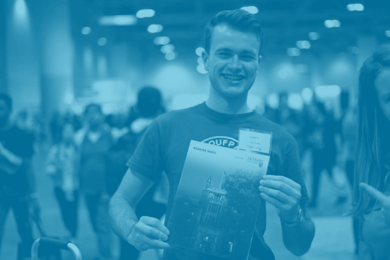 A blue duotone image of a McMaster student holding up a viewbook at the Ontario Universities fair