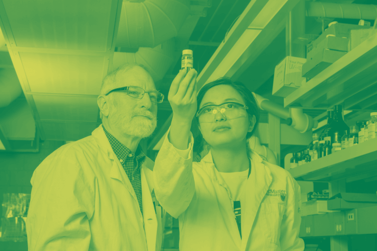 A green-yellow duotone image of a man and a woman standing in a lab, examining a vial