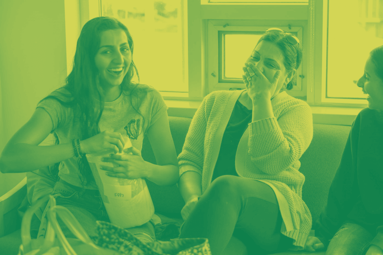 A green yellow duotone image of a student and parent sitting on a couch andlaughing