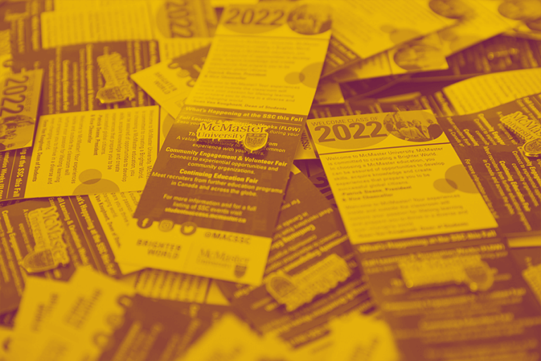 A yellow maroon duotone image of a table with McMaster University pins and brochures