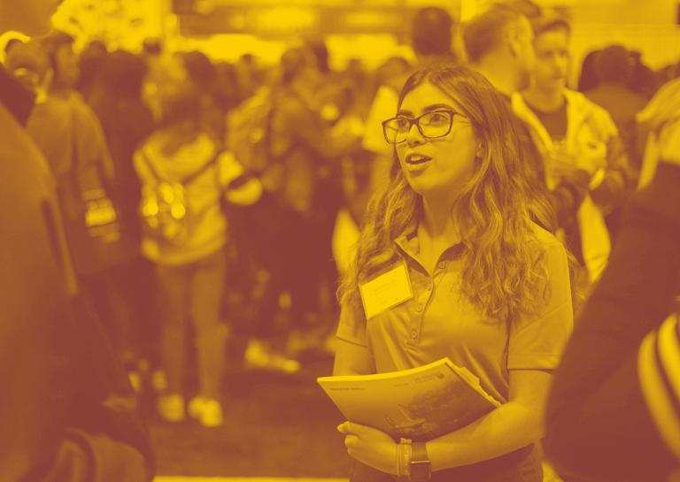 A yellow maroon duotone image of a McMaster student representative at the Ontario Universities Fair