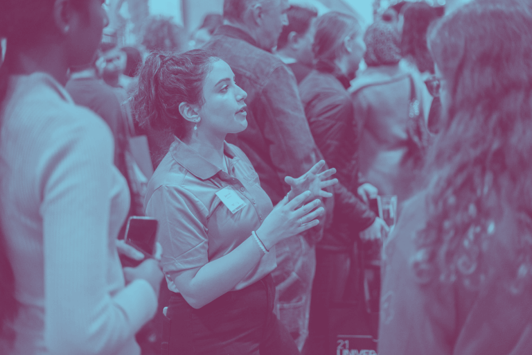 A blue duotone image of a McMaster student representative talking to parents at the Ontario Universities Fair