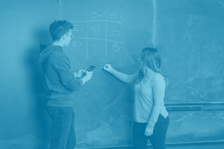 A blue green duotone image of two students solving an equation on a chalkboard
