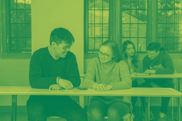 A green yellow duotone image of four students studying in a classroom