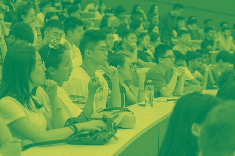 A green yellow duotone image of a large group of students in a lecture hall