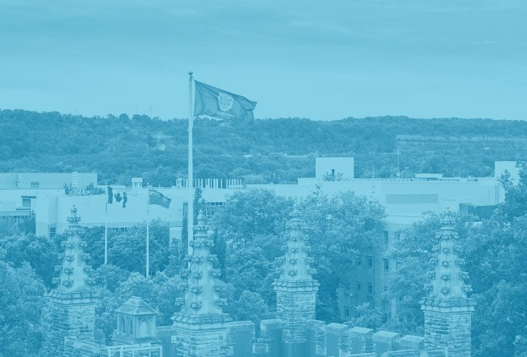A blue yellow duotone image of a drone shot of the flag mounted on University Hall on campus