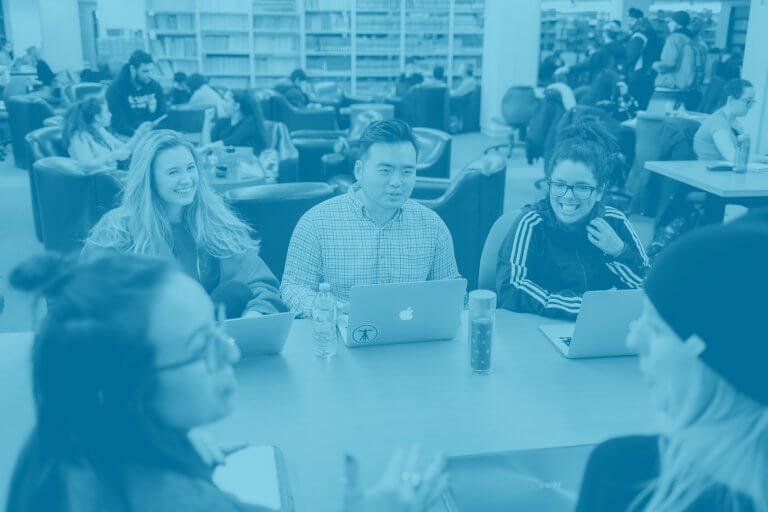 A blue green duotone image of a group of students sitting together and talking at a library table