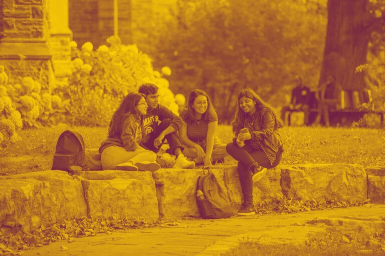 A maroon yellow duotone image of four students sitting together on large rocks on campus and talking