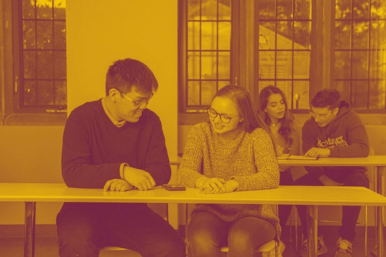 A maroon yellow duotone image of four students studying in a classroom