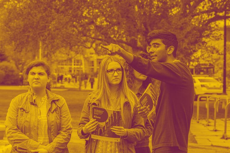 A maroon yellow duotone image of a McMaster student giving directions to three campus visitors