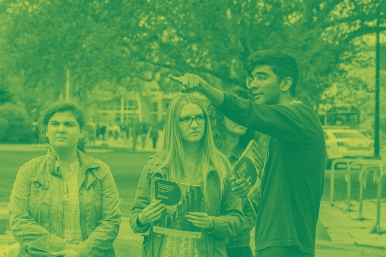 A green yellow duotone image of a McMaster student giving directions to three campus visitors