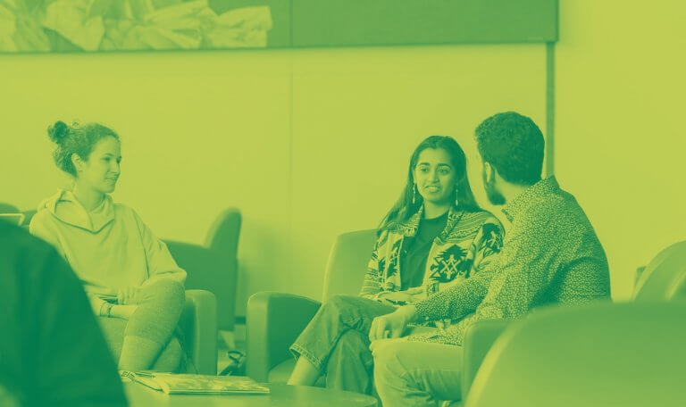 A green yellow duotone image of three students sitting on couches in the library and talking