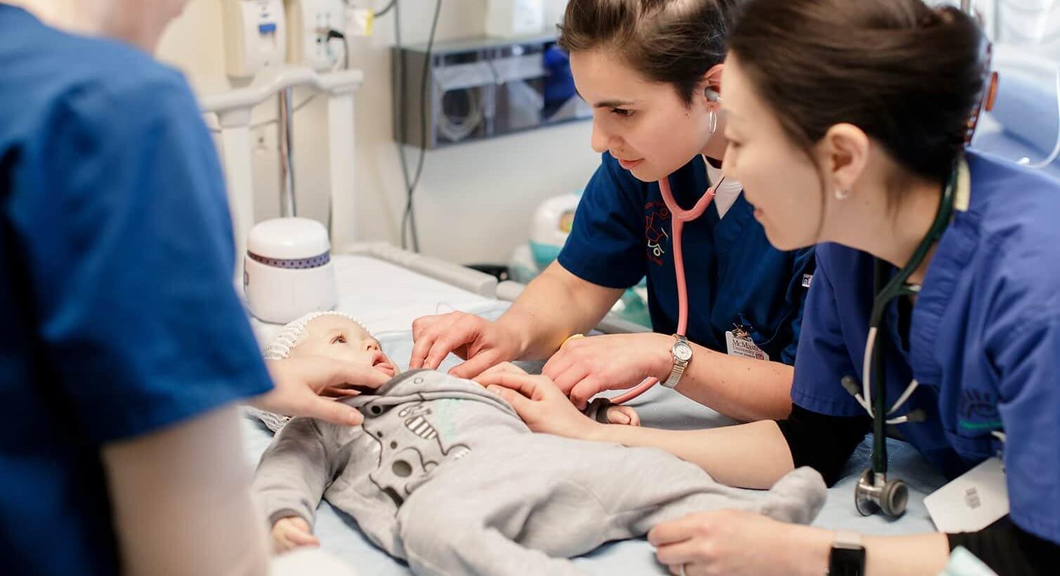 Three nurses examining a baby at the McMaster Children's hospital