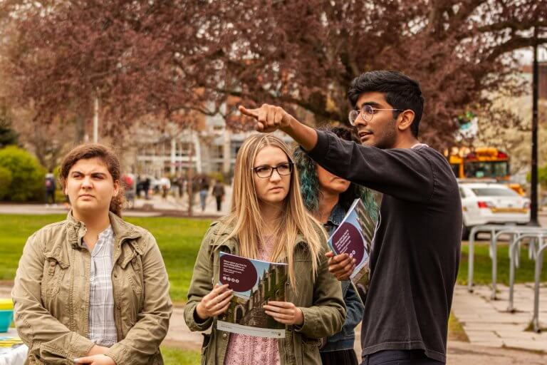 A university student giving directions to three campus visitors