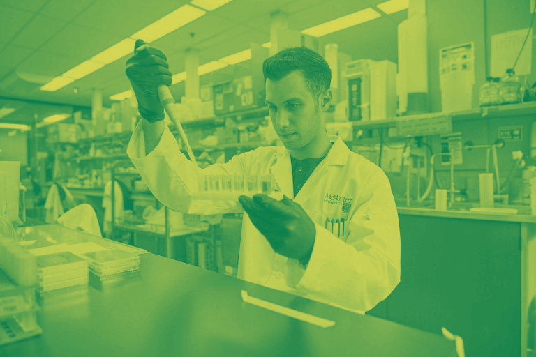 A green and yellow duotone image of a man in a labcoat working in a lab
