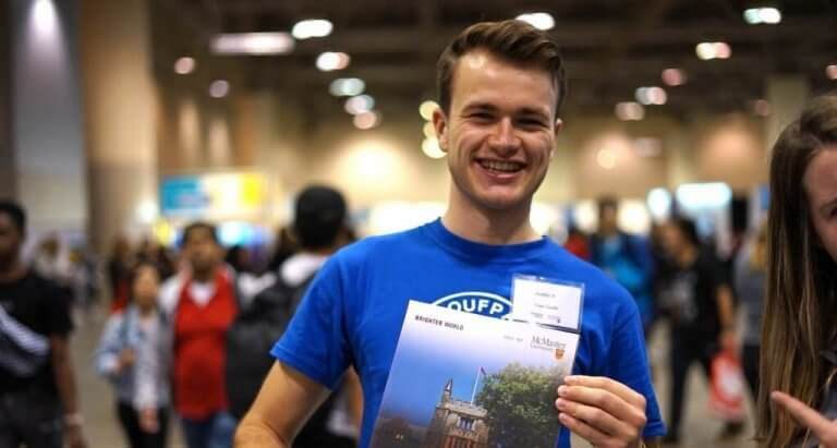 A McMaster student holding up a viewbook at the Ontario Universities Fair