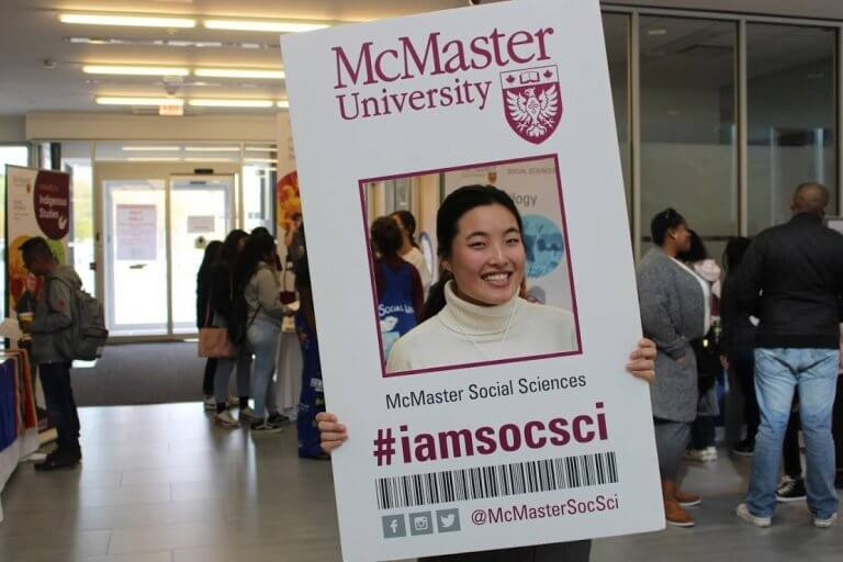 McMaster student holding up a life-sized cutout of a student card
