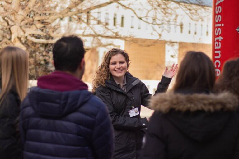 Student tour guide showing people around McMaster campus
